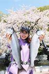 51センチのビワマス(左)を釣り上げた村西アナ。琵琶湖岸の八重桜の前で笑顔がはじける(撮影・澄田垂穂)